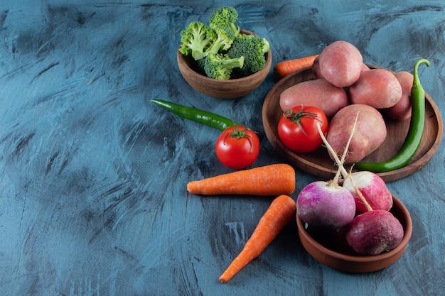 青い背景にさまざまな新鮮な野菜の束。
