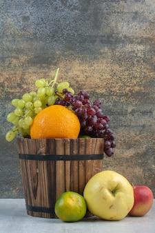 木製のバケツにさまざまな果物の束