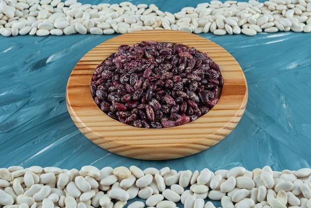 青い表面に散らばった様々な生豆の束。 無料写真