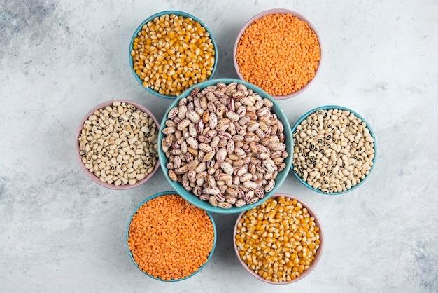 さまざまな生の豆、トウモロコシ、赤レンズ豆をボウルに入れた束。