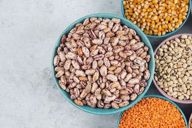 대리석 표면에 다양한 요리하지 않은 콩, 옥수수 및 빨간 렌즈 콩의 무리.