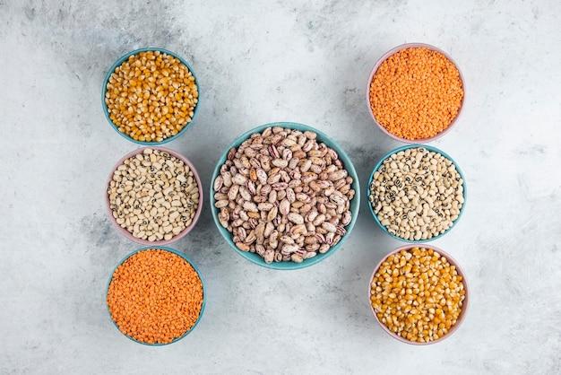 Букет из различных сырых бобов, кукурузы и красной чечевицы на мраморной поверхности.