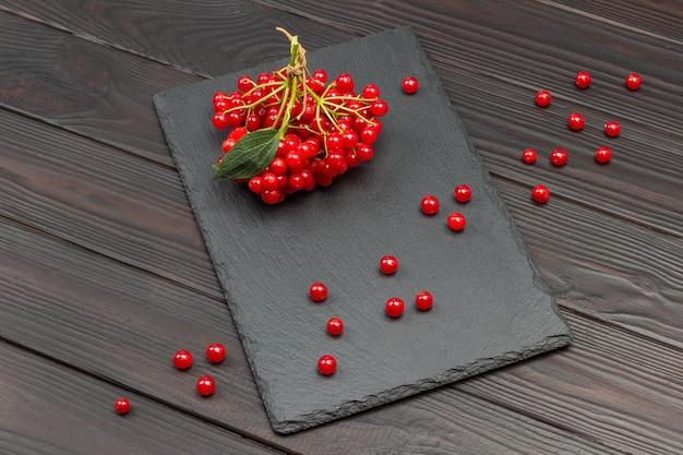 黒のスタンドにガマズミの小枝の束。テーブルの上の赤いベリー。暗い木の背景。上面図