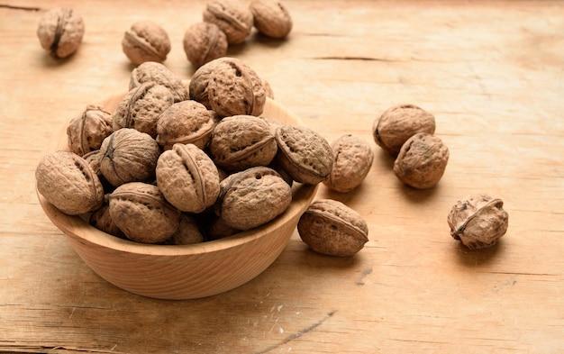 Связка грецких орехов в деревянной тарелке на столе, крупным планом