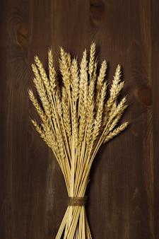 小麦の穂の束が暗褐色の木製の背景にクローズアップ穀物の秋の収穫