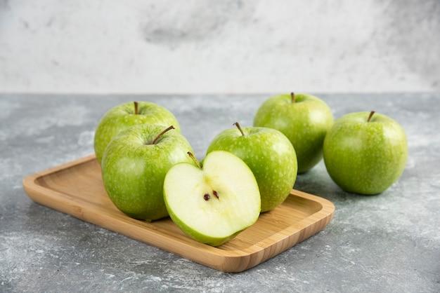 나무 접시에 전체 및 얇게 썬 녹색 사과의 무리.