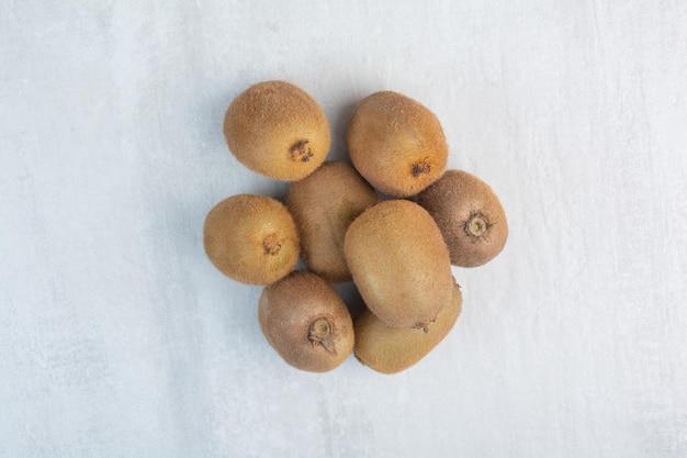 石の背景に丸ごとキウイフルーツの束。高品質の写真