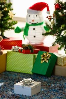 自宅での休日のお祝いの間にクリスマスツリーと雪だるまの近くの床に置かれた包まれたプレゼントの束