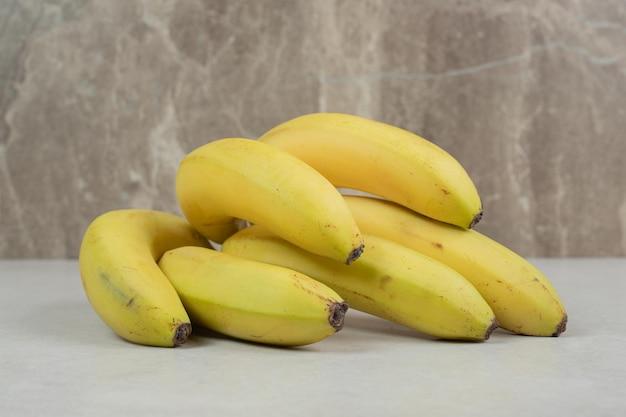 Связка желтых бананов на сером столе