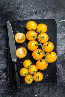 대리석 보드에 노란색 체리 토마토의 무리입니다. 검은 배경. 평면도.
