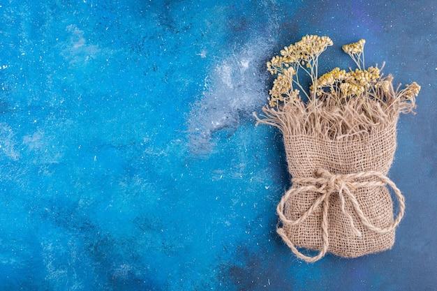 Букет из желтых засушенных цветов в мешковине на синей поверхности.