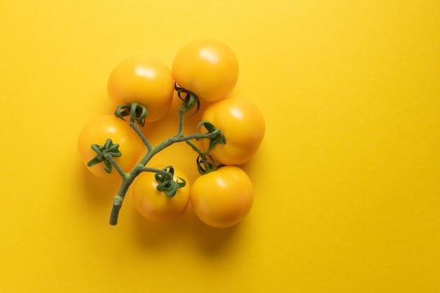 黄色のトマトの束、創造的で黄色の背景に美しい