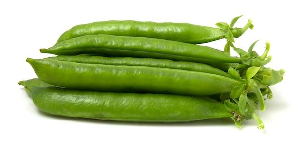 白い背景で隔離の若いエンドウ豆の鞘の束。