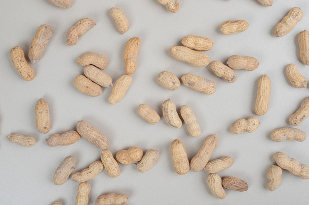 Bunch of organic peanuts on beige surface