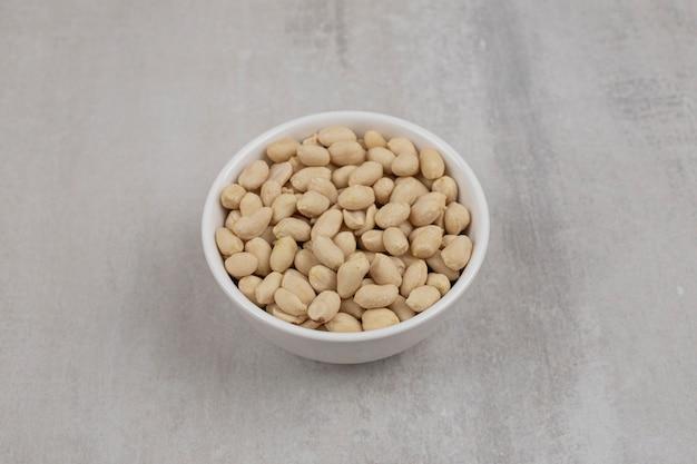 Mazzo di arachidi sbucciate in una ciotola bianca.