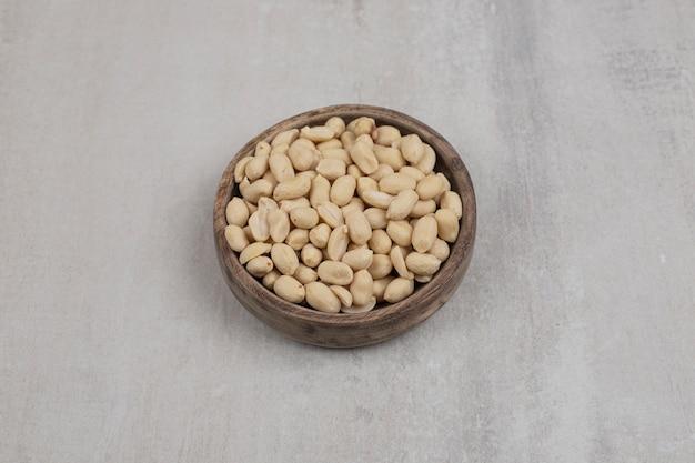 Mazzo di arachidi sbucciate in ciotola di legno.