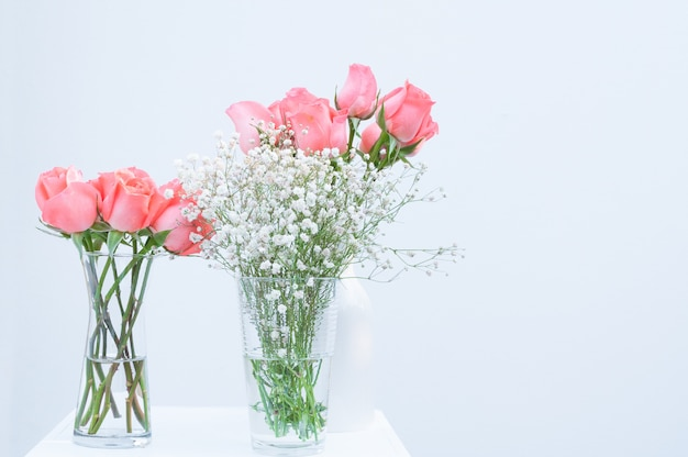 Bunch of pink rose eustoma flowers in glass vase on white background