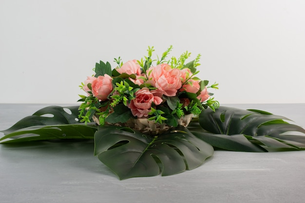 Bunch of pink roses with leaves on grey surface