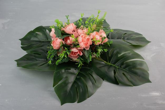 Mazzo di rose rosa con foglie sulla superficie grigia.