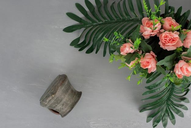Mazzo di rose rosa con foglie e vaso su superficie grigia