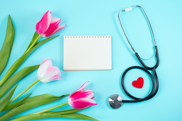 Bunch of pink tulips and stethoscope on blue desk.