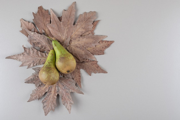 Bunch of plane tree leaves under two pears on marble