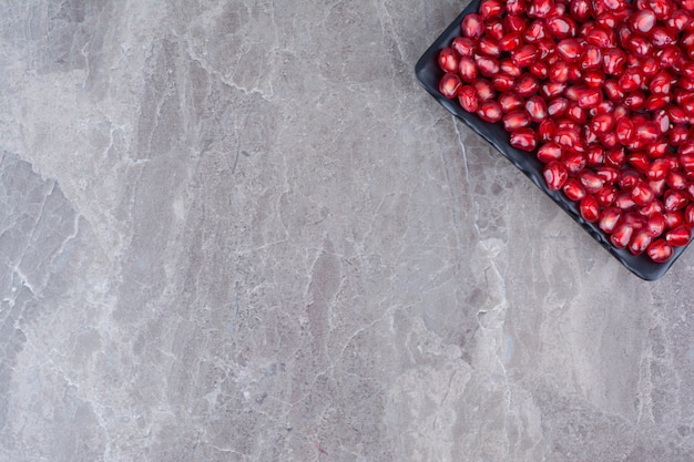 Bunch of pomegranate seeds on black plate.