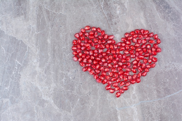 Bunch of pomegranate seeds formed like heart.