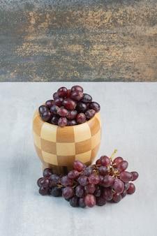 Grappolo d'uva viola nel secchio e sul tavolo