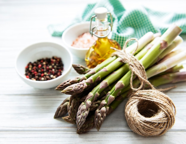 Bunch of raw asparagus stems with different spices and ingredients on wooden surface