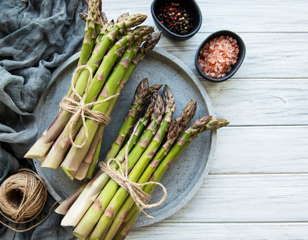 Bunch of raw asparagus stems  on wooden surface