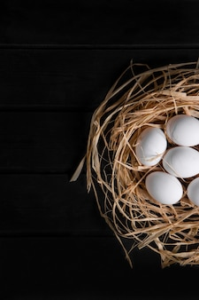 Bunch of raw fresh eggs in bird's nest on black surface. high quality photo