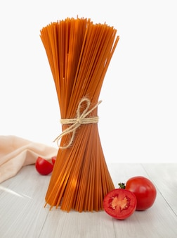 Bunch of raw italian red pasta with tomatoes on light background
