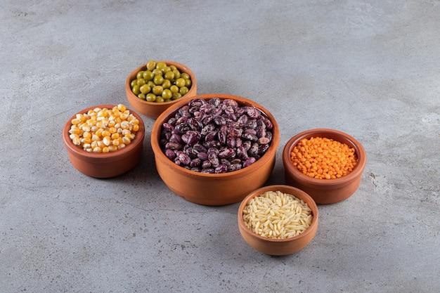 Mazzo di lenticchie crude, fagioli e riso su fondo di pietra.