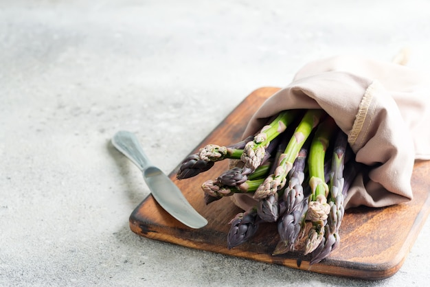 Bunch of raw organic asparagus spears on board ready for cooking healthy diet food on light grey marble.