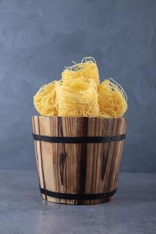 Bunch of raw pasta nests in wooden bucket.