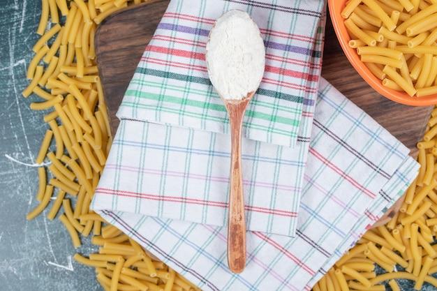 Mazzo di pasta cruda su tavola di legno con tovaglia e farina. foto di alta qualità