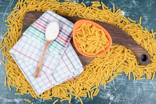 Bunch of raw pasta on wooden board with tablecloth and flour.