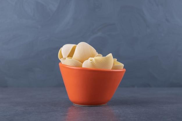 Bunch of raw shell pasta in orange bowl.