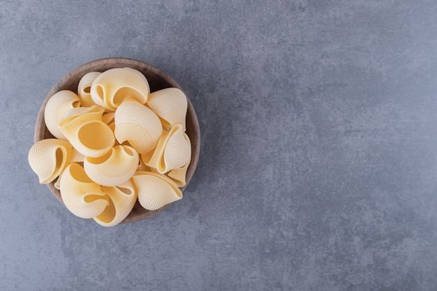 Bunch of raw shell pasta in wooden bowl.