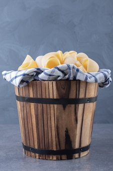 Bunch of raw shell pasta in wooden bucket.