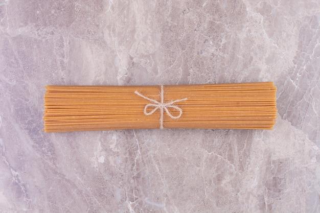 Un mucchio di spaghetti crudi su uno spazio grigio.