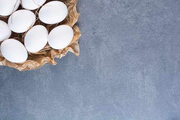 Bunch of raw white eggs placed on stone table.