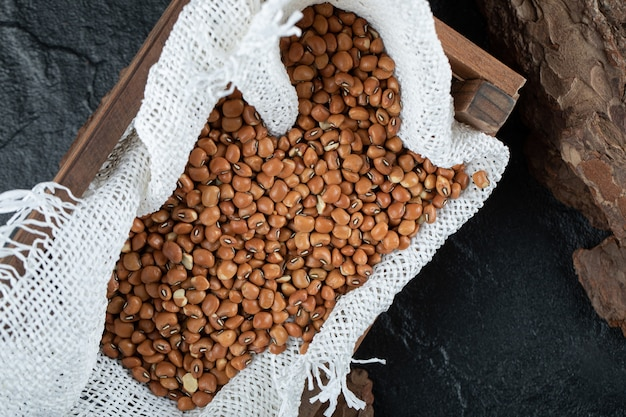 Bunch of red beans in wooden box with burlap.