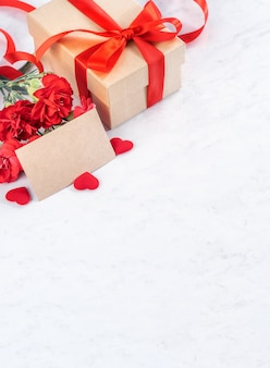 Bunch of red carnation with gift box for mother's day greeting concept.