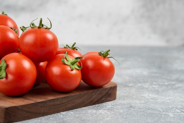 Bunch of red fresh tomatoes on wooden cutting board.