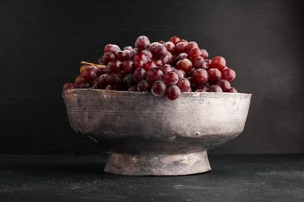 A bunch of red grapes in a metallic bowl.