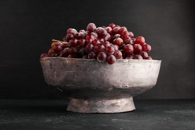 Un grappolo d'uva rossa in una ciotola metallica.