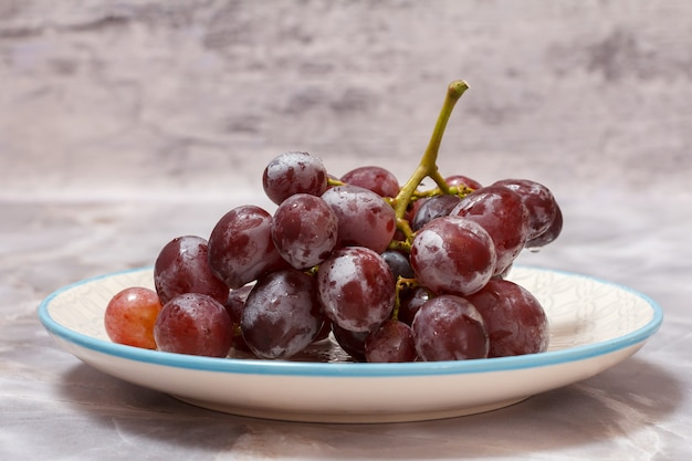 Bunch of red grapes on a white plate with gray background.