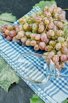 Un grappolo d'uva rossa e un bicchiere di vino sulla tovaglia blu. foto di alta qualità